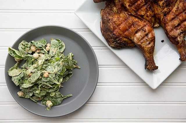 A plate of tandoori masala spiced chicken with a side of creamy chickpea and spinach salad.