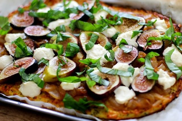 A toasted cauliflower-crusted pizza topped with cheese, figs and fresh basil.