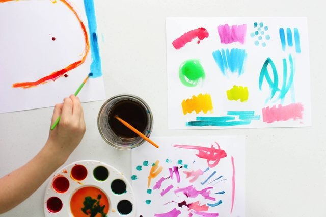 Kid painting with watercolors.