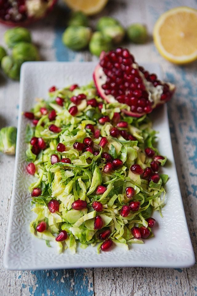 A colorful plate of Brussels sprouts sprinkled with pomegranate arils.