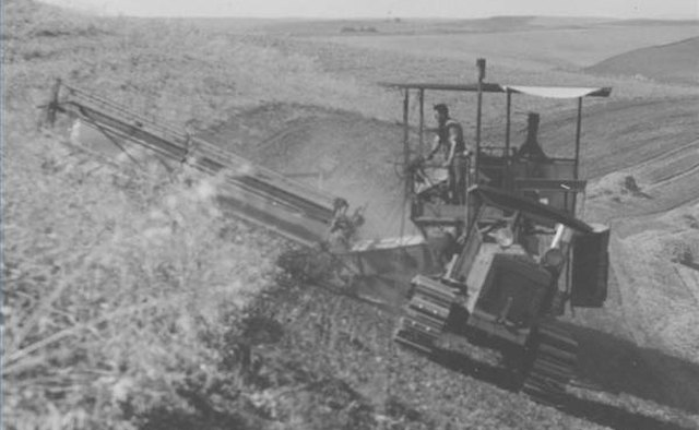 A sidehill combine harvesting peas on a hillside in 1937.