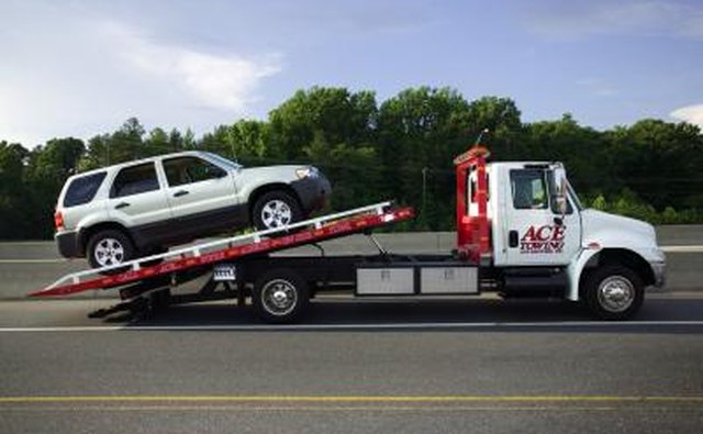 SUV being loaded onto a flatbed tow truck