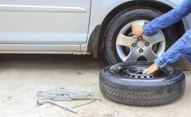 Woman removing a tire along the roadside
