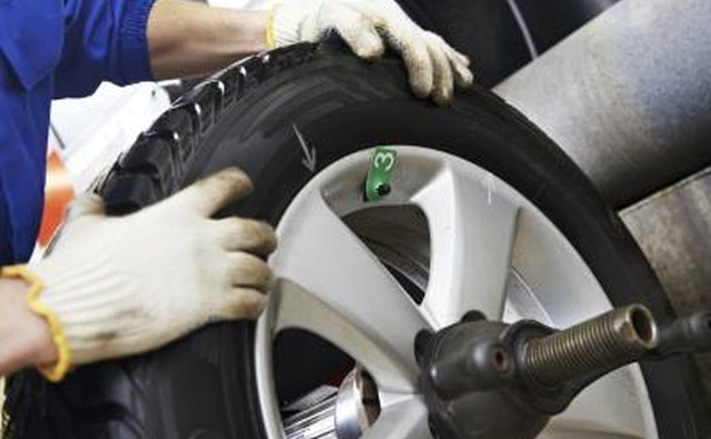 A close-up of a mechanic handling the wheel of a car.