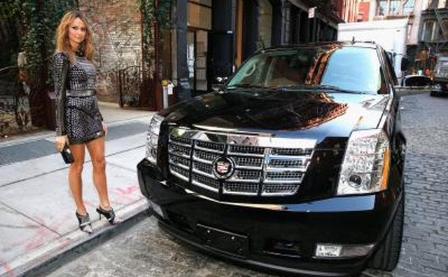 A woman standing next to an Escalade