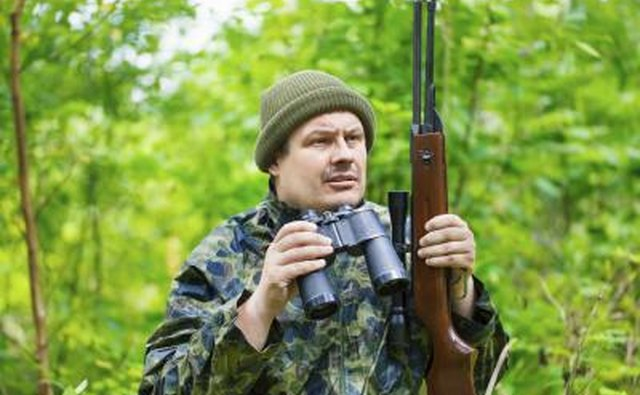 A hunter holds binoculars and a rifle.