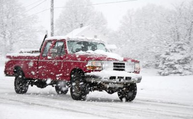 Pick up truck driving in the snow.