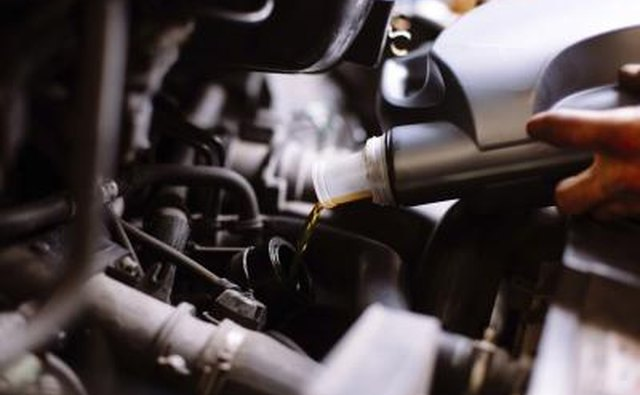Filling oil in car engine.