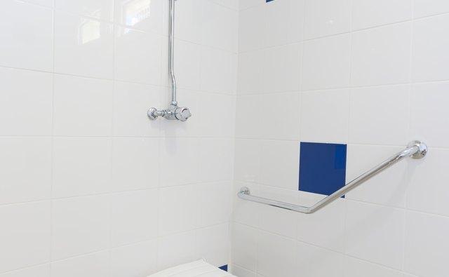 Foldable bath aid chair in shower