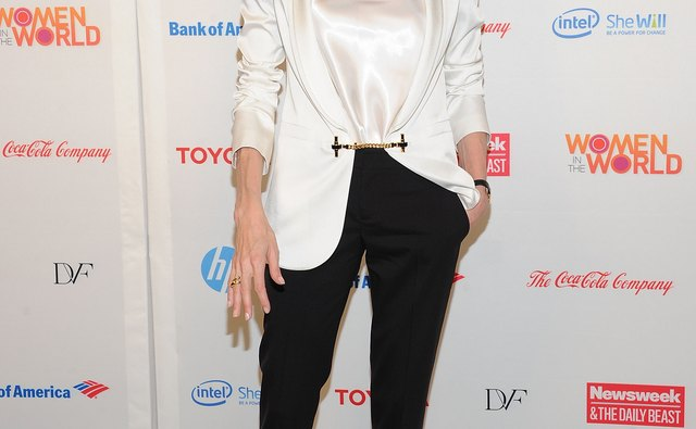 Actress Angelina Jolie pairs black straight-legged pants with a billowy satin blouse and white blazer for a classically chic semi-formal ensemble.