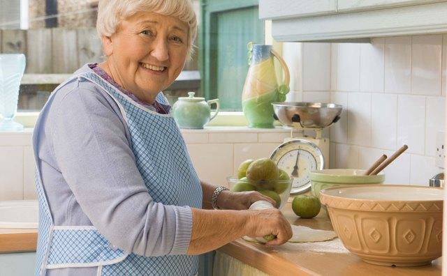 Senior woman prepares food in kitchen