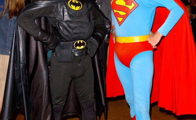 Two men dressed as Batman and Superman pose for a photo at a tradeshow.