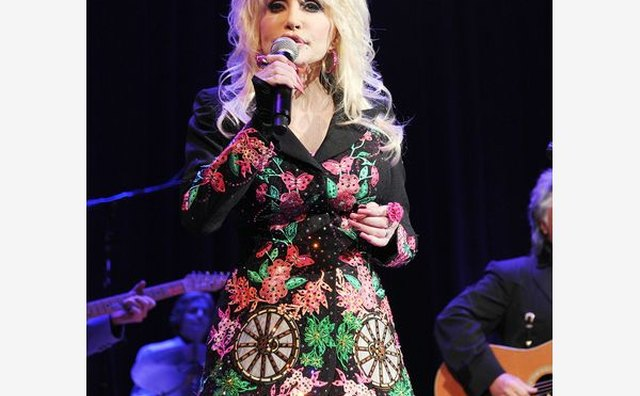 Dolly Parton serenades crowds in a wagon wheel print.