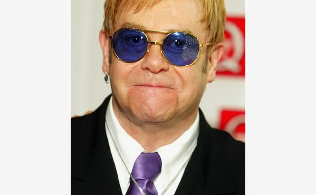 Sir Elton John punches up a classic formal look with a splash of color.