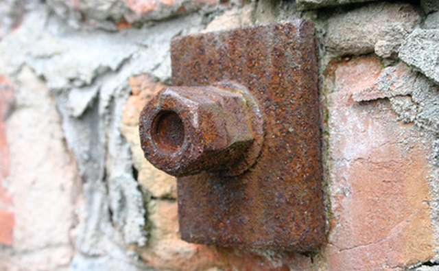 Nuts and bolts support a brick wall.