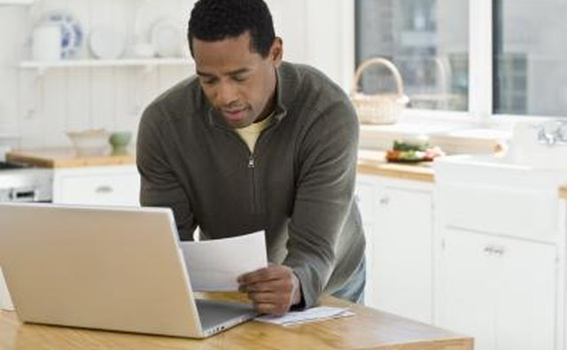 Man using laptop, reading paperwork