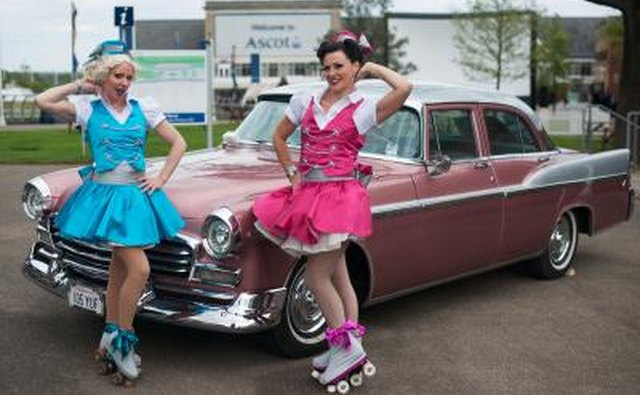 Girls in 1950's costumes pose by vintage automobile