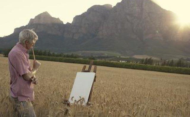 Senior man painting a landscape scene