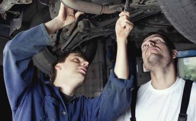Mechanics looking at wheel bearings