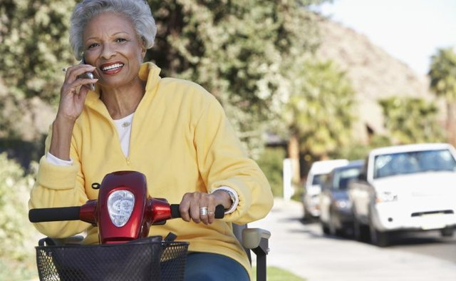 Senior woman using scooter on sidewalk