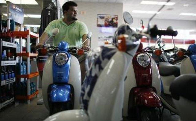 Man looking at Honda scooters on showroom floor.