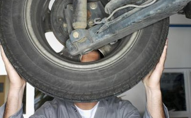 Mechanic inspecting wheel