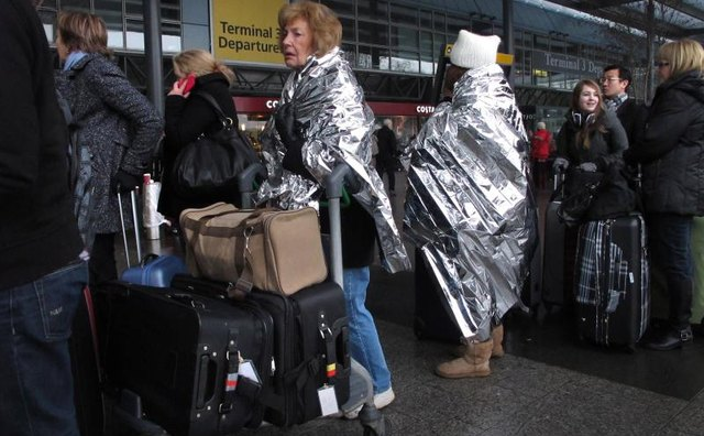 Women wrapped in thermal blankets at airport.