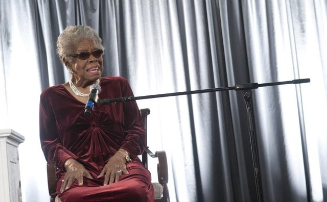 Maya Angelou sitting in front of microphone