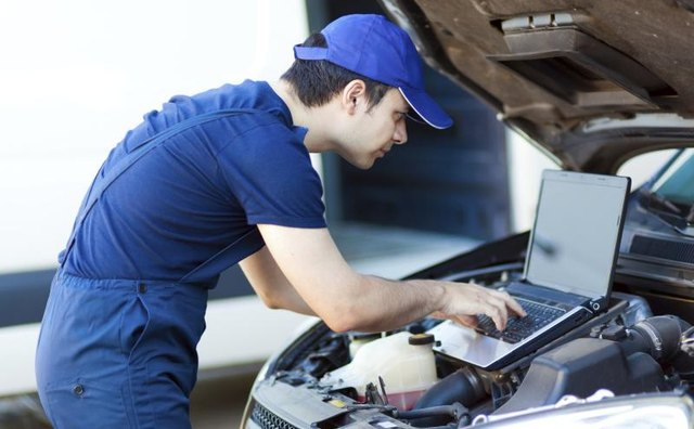A mechanic uses a laptop to examine a car engine