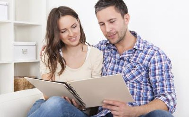 Couple sitting together on couch looking at booklet of questions