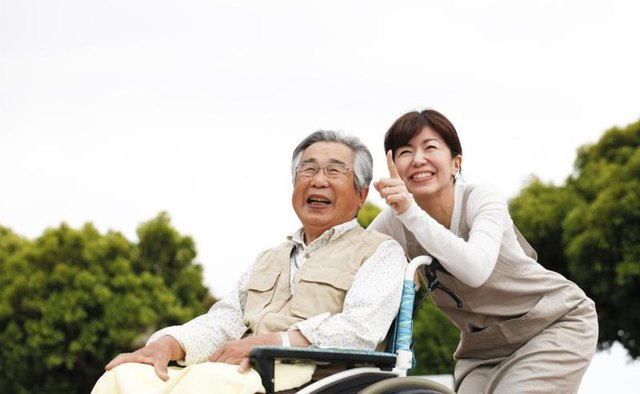 Senior man in wheelchair accompanied by his daughter