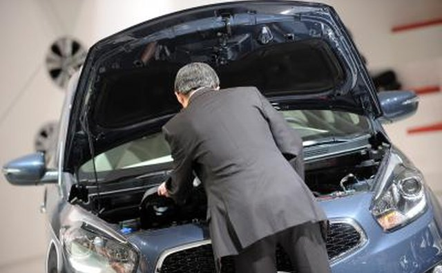 Man inspects engine of a KIA automobile