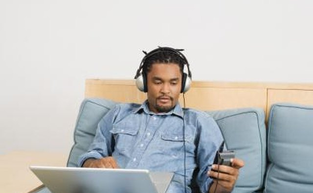 Man using headphones with laptop