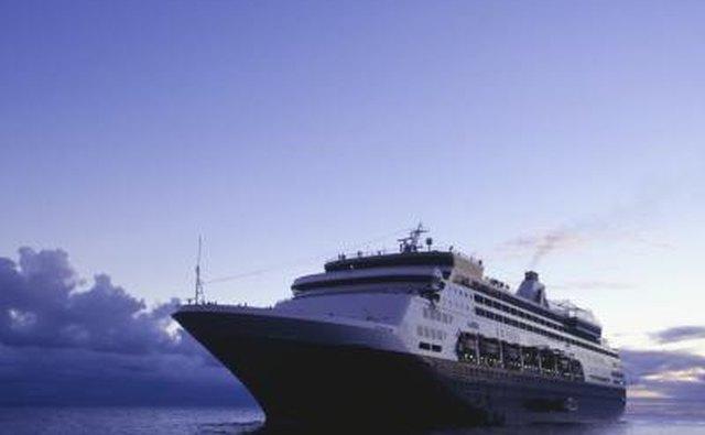 A cruise ship sails the ocean at dusk.
