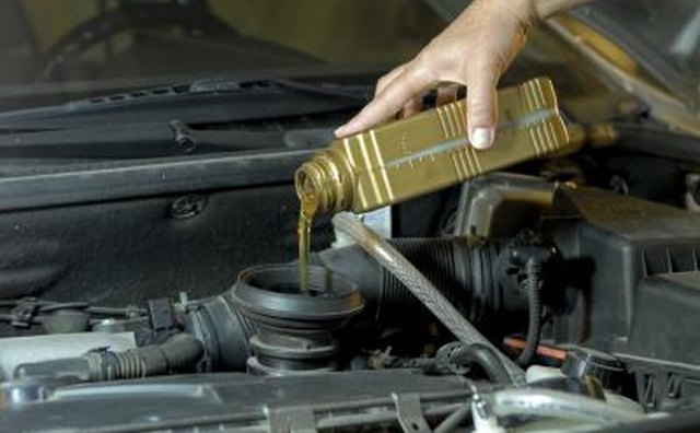 Motor oil being poured into older engine