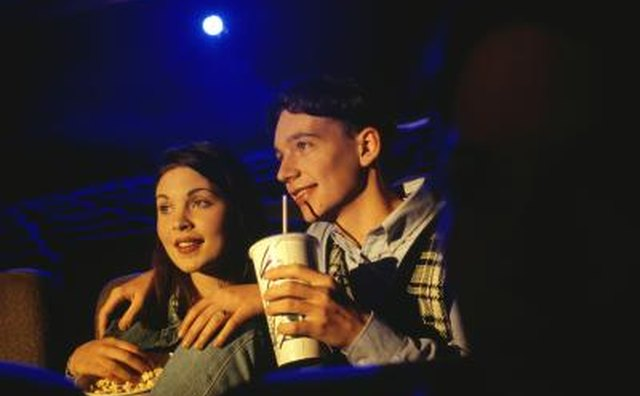 A young couple sharing a drink in a movie theater.