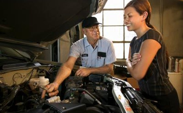 Mechanic and woman looking under hood of car.