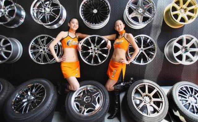 Models stand with Dunlop tires exhibit at a car expo in Shanghai, China