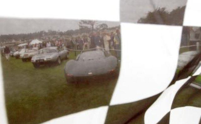 Row of vintage Jaguars seen through checked flag at Pebble Beach, CA.