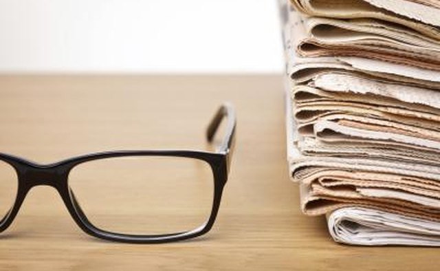 A pair of black eyeglass frames and a stack of newspapers on a desk.