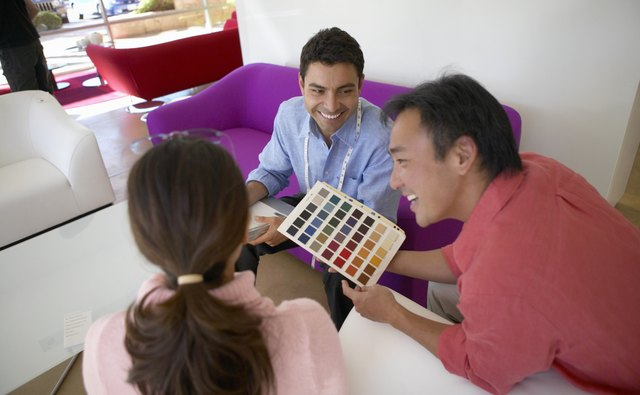 Couple With a Shop Assistant in a Furniture Shop Looking at a Colour Swatch