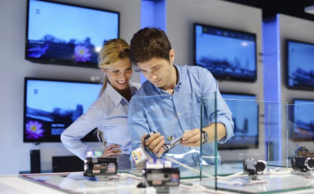 couple in consumer electronics store buying photo camera
