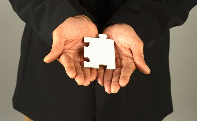 Close up of a person holding a puzzle piece