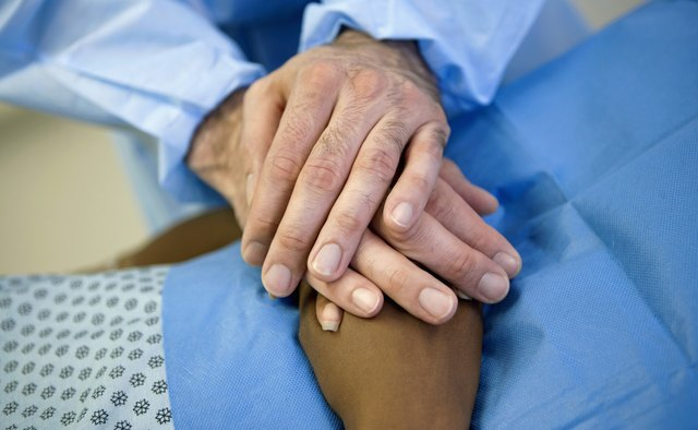Healthcare worker holding hands with patient