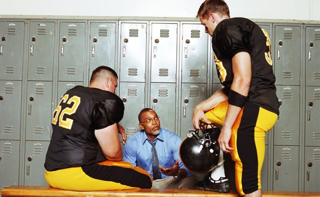 Football players listening to coach in locker room