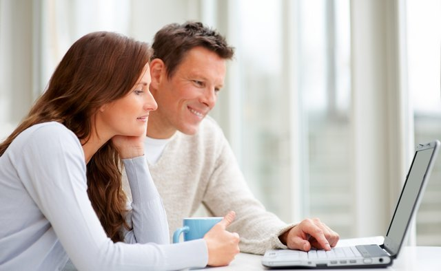 Couple using a laptop and smiling