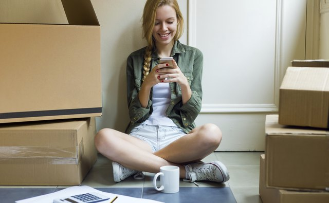 Young beautiful woman with mobile phone in her new house.