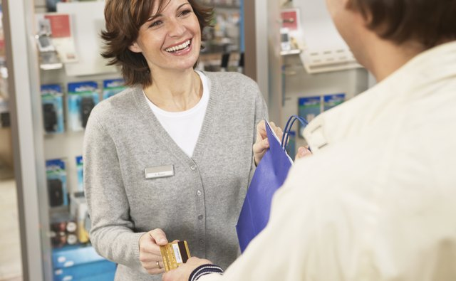 How long should a business keep credit card receipts bizfluent man giving woman card at shop counter smiling close up reheart Gallery