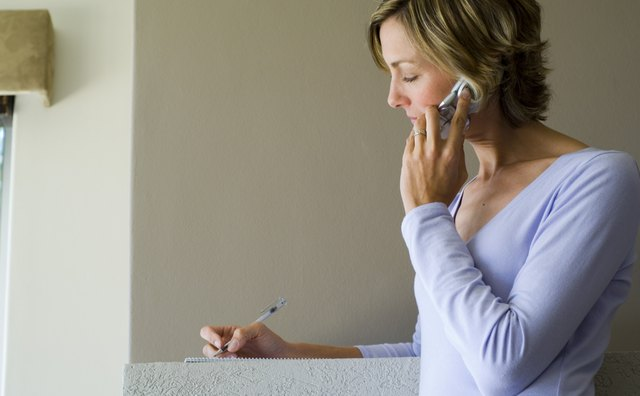 Woman talking on phone and writing