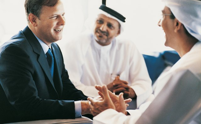 Businessman Having a Discussion With Two Other Businessmen Wearing Traditional Middle Eastern Dress